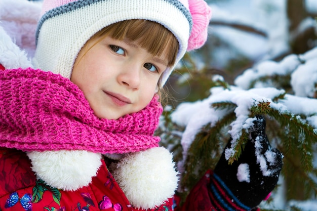 Portrait of pretty little girl in winter clothes near snow covered pine tree