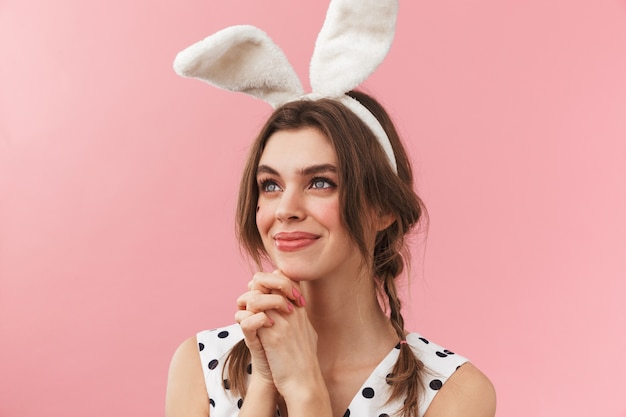 Portrait of a pretty lovely girl wearing bunny ears standing isolated, begging