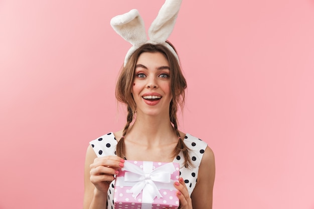 Portrait of a pretty lovely girl wearing bunny ears standing isolated, holding gift box