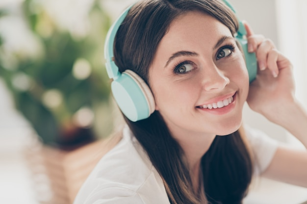 Portrait of pretty lovely girl with wireless headset listening music wear casual style outfit in house indoors