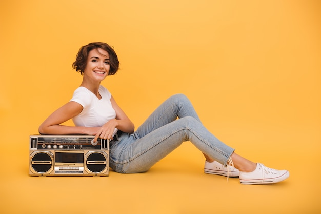Portrait of a pretty lovely woman sitting with record player