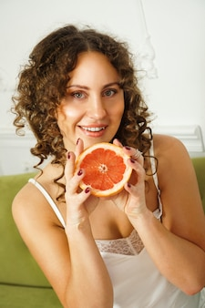 Portrait of pretty middle-aged woman with curly hair with grapefruit at home - light room. happiness, beauty and health - vertical photo