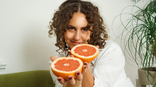 Portrait of pretty middle-aged woman with curly hair with grapefruit at home - light room