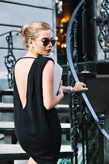 Modello grazioso ritratto in abito corto nero con schiena nuda sulle scale all'aperto. sta guardando in basso.