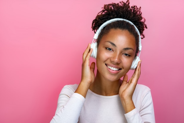 Portrait of a pretty mulatto girl in earphones listening to music