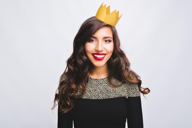 Портрет довольно позитивной девушки в модном платье с длинными вьющимися волосами брюнетки в желтой короне на белом пространстве