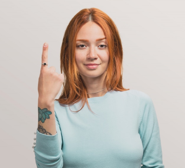 Portrait of a pretty redhead girl doing number one gesture