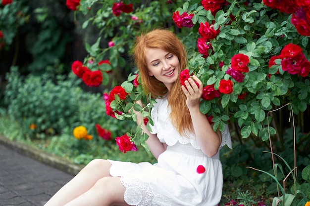 Portrait of a pretty redhead girl dressed in a white light dress on a background of blooming roses.