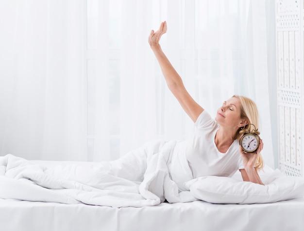 Portrait of pretty senior woman holding a clock