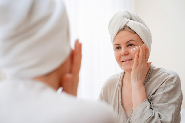 Portrait pretty senior woman with hands on her face mirror at home after bathroom skin care