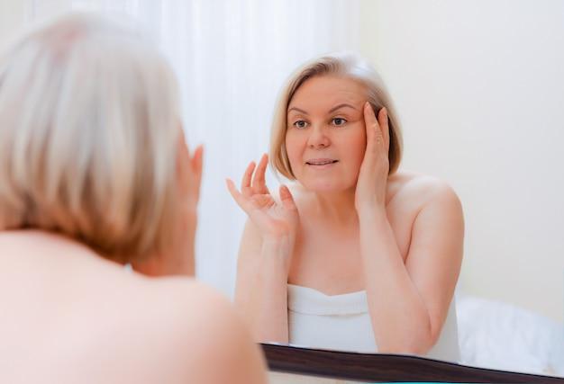 バスルーム後自宅で彼女の顔の鏡に手を持つ肖像画かなり年配の女性50-60年後のスキンケア