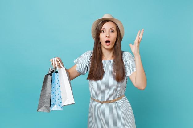 肖像画はかなりショックを受けた悲しい美しい白人女性の夏のドレス、青いパステル背景で隔離の買い物後の購入でパッケージバッグを保持している麦わら帽子。広告用のスペースをコピーします。