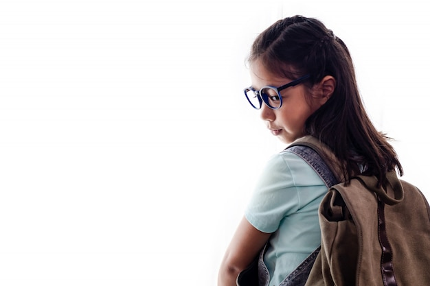 Portrait of pretty smart asian schoolgirl or kid with books and backpack isolated
