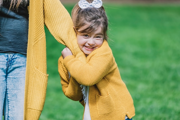 Portrait of a pretty smiling little child girl standing in park outdoors
