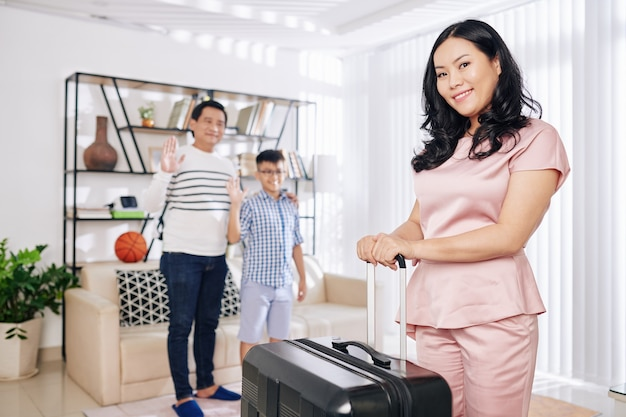 Portrait of pretty smiling mature asian woman standing in living room with suitcase, her husband and son waving her