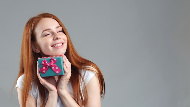 Portrait of a pretty smiling redhead girl holding small gift box with ribbon. studio portrait