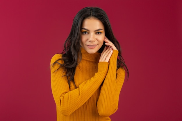 Portrait of pretty smiling stylish brunette hispanic woman in yellow autumn winter fashion dress sweater posing isolated on red wall