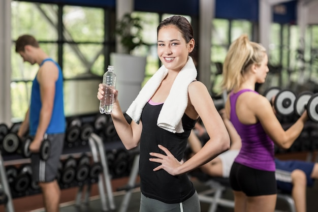 Portrait of pretty smiling woman with water bottle at gym