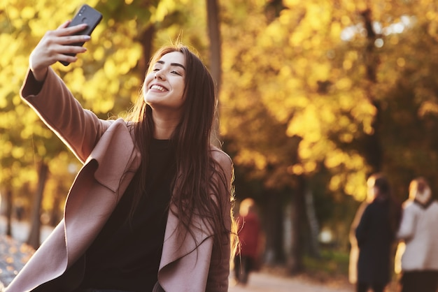 Portrait of pretty, smiling young brunette girl making selfie with a black smartphone, wearing casual coat in a sunny, yellow, autumn garden on the blurry background.