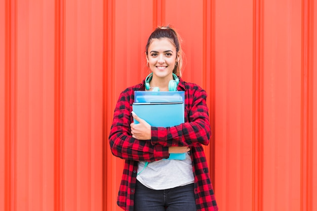 Portrait of pretty student in smart casual holding books in hand standing against wall looking to camera
