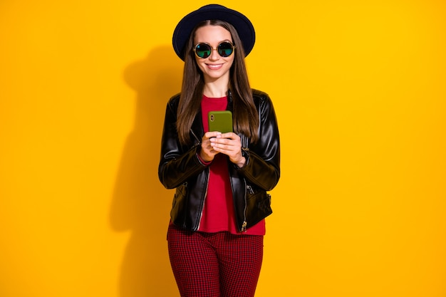 Portrait of pretty stylish cheerful girl using app phone