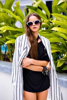 Ritratto di donna abbastanza elegante indossando occhiali da sole vestito elegante bianco e nero e giacca alla moda blogger