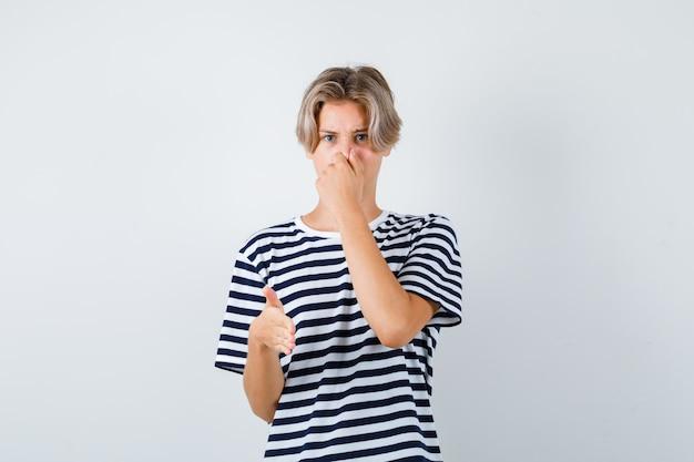 Ritratto di un bel ragazzo adolescente che odora qualcosa di terribile, pizzicando il naso, mostrando il segnale di stop in maglietta a righe e guardando disgustato vista frontale