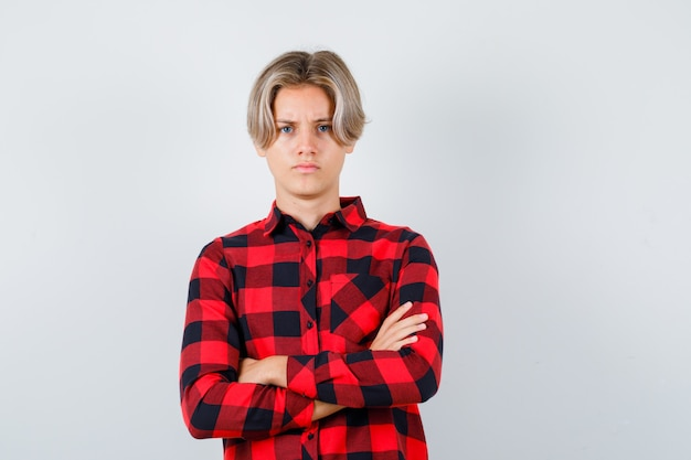 Portrait of pretty teen boy standing with crossed arms in checked shirt and looking displeased front view
