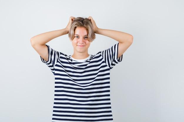 Ritratto di un bel ragazzo adolescente con le mani sulla testa in maglietta a righe e guardando allegro vista frontale