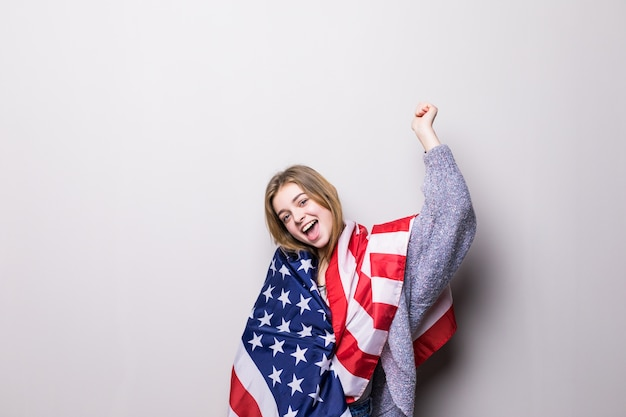 Portrait of pretty teen girl holding usa flag isolated on gray. 4th july celebration.