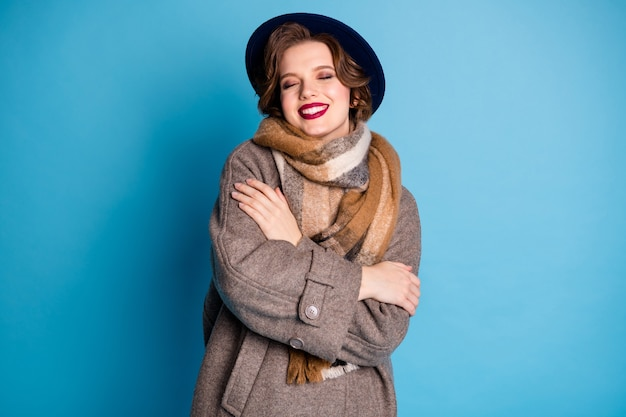 Portrait of pretty traveler lady hold herself shoulders eyes closed enjoy warmth soft pleasant wool wear stylish casual long grey coat hat plaid scarf .