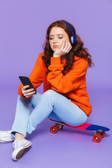 Portrait of a pretty upset young redheaded woman sitting on skateboard over violet, listening to music with headphones