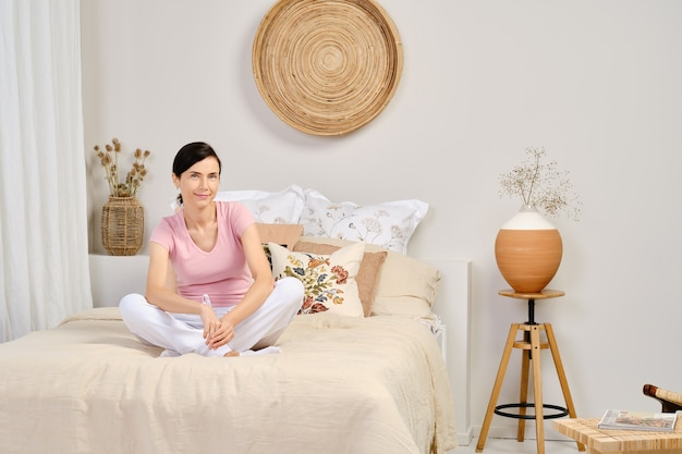 Portrait of pretty woman in casual clothes sitting on bed at home