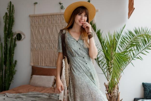 Portrait of pretty woman in dress enjoying cozy home