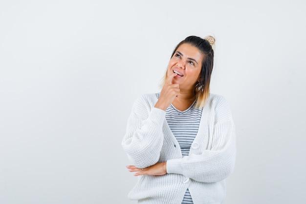 Ritratto di donna graziosa che tiene il dito sul labbro inferiore