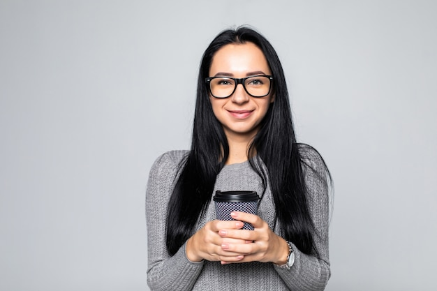 Portrait of a pretty woman holding takeaway coffee cup isolated over gray wall