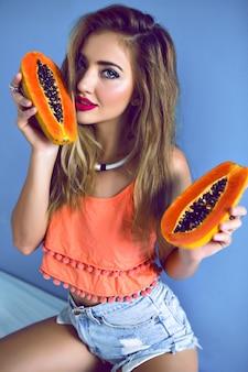 Ritratto della donna graziosa che tiene la papaia tropicale dolce saporita