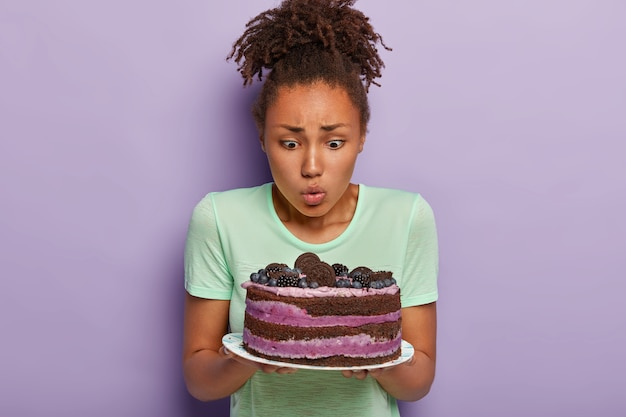 Il ritratto della donna graziosa tiene il piatto con la grande torta appetitosa saporita