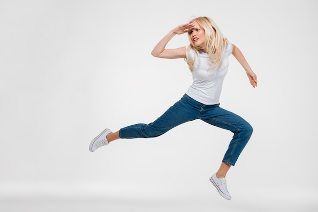 Portrait of a pretty woman jumping and looking