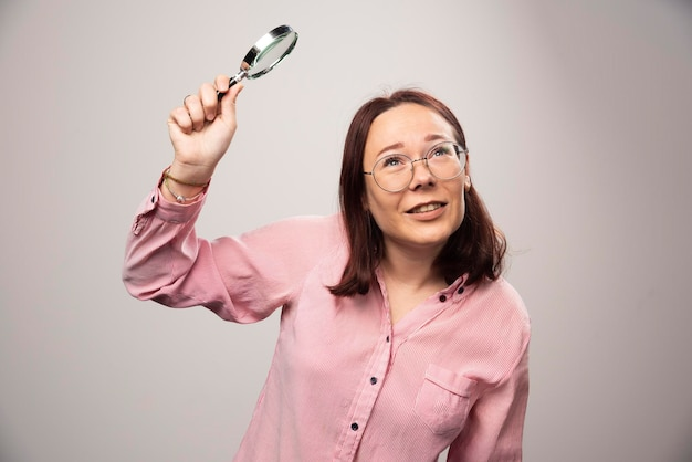 Portrait of pretty woman in pink clothesholding a magnifying glass. high quality photo