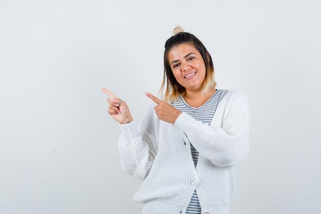 Ritratto di una bella donna che punta all'angolo in alto a sinistra in maglietta, cardigan e sembra allegra