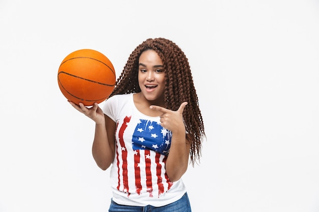 Portrait of pretty woman rejoicing and holding basketball during game while standing isolated against white wall