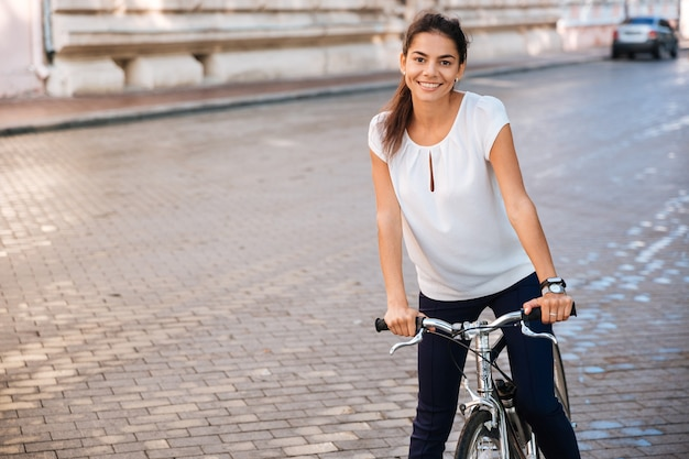 Portrait of a pretty woman riding bicycle in the city street and looking at front
