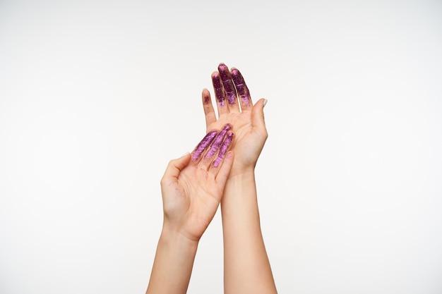 Ritratto delle mani eleganti della donna graziosa che dimostrano i palmi e si toccano delicatamente l'un l'altro, essendo isolato su bianco