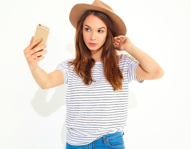 Portrait of a pretty woman in summer hipster clothes taking a selfie isolated on white wall