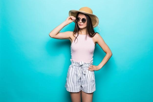 Ritratto di donna graziosa in occhiali da sole e cappello su blu colorato. concetto di estate.