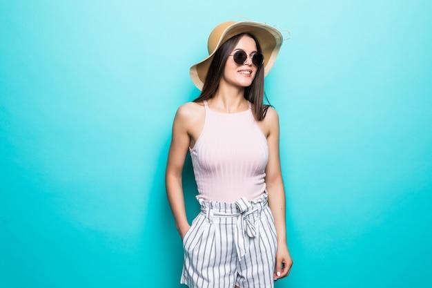 Ritratto di donna graziosa in occhiali da sole e cappello sopra la parete colorata blu. vocazione estiva.