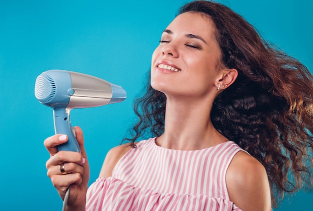Portrait of a pretty woman using a hair dryer on blue wall