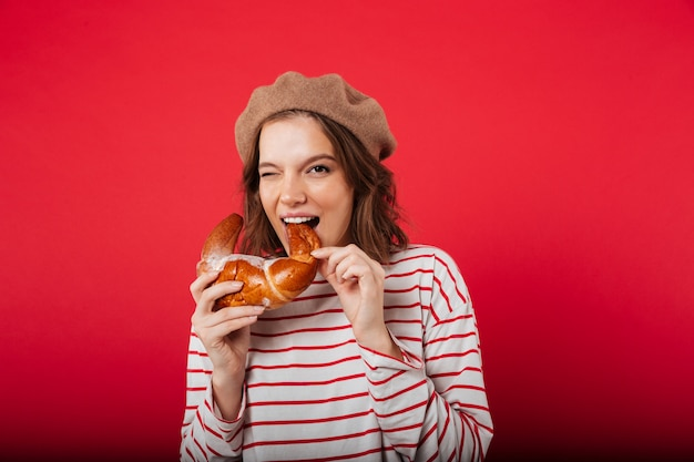 Portrait of a pretty woman wearing beret eating croissant