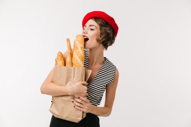 Portrait of a pretty woman wearing beret holding paper bag
